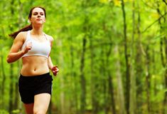 Forest Runner. Beautiful young woman runner in a green forest stock image