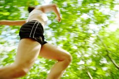 Forest Runner. Beautiful young woman runner in a green forest stock photo