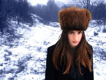 Forest's fairy. A view of young woman with bright reddish hair and wearing a tall Cossack fur hat, in the forest on a gray winter day stock photos