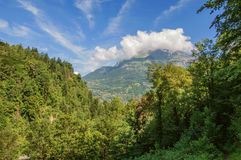 Forest in Saint-Gervais-Les-Bains with alpine mountains landscape. In the background, French Alps, blue sky and clouds stock images