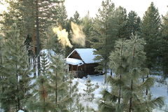 Forest shelter for hunters in the Siberian taiga in winter. Warm house with a stove for temporary accommodation and rest in the deep thicket of pine trees Stock Images