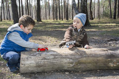 In the forest, sitting on a log, two boys, one playing with a to Royalty Free Stock Photography