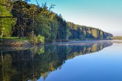 Forest and sky reflected in the calm blue water of Lake Forest. Early morning. Relax and silence Stock Photography
