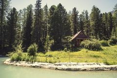 Forest and small house in it in summer day. Wooden two-storey cottage. Cabin in the woods. The tourist base for a stay in the fore. St royalty free stock photography