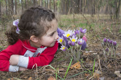 In the forest in the spring, a little girl lies on the ground an Stock Photo