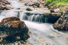 Forest stream running over mossy rocks in Alps Italian Dolomite stock photography