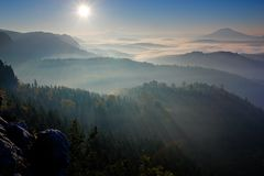 Forest with sun rays. Morning with sun. Cold misty foggy morning in a fall valley of Bohemian Switzerland park. Hills with fog, la royalty free stock image