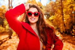 Forest and sunny weather. A portrait of a beautiful young woman wearing sunglasses in a sunny autumn forest. Lifestyle, autumn fashion, beauty stock photo
