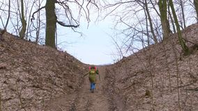 From the forest to the hill, runs out, a teenager in a jacket rises, with a stick in his hand, like a traveler on foot. A walking tour. goal achievement stock footage