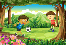 A forest with two boys playing soccer Royalty Free Stock Image