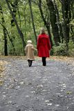 Forest walk. Mother and the daughter walking by the autumn forest road Stock Images