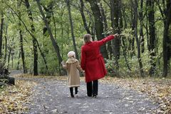 Forest walk. Mother and the daughter walking by the autumn forest road Royalty Free Stock Photography