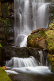 Forest waterfall. A rocky waterfall photographed with a slow shutter speed creating soft flowing water Stock Image