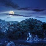 Forest waterfall on hill in fog at night. Small waterfall comes out of a forest on a rocky hill and falls in river with fog at night in full moon light Stock Photo