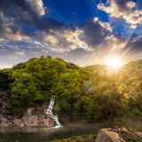 Forest waterfall on hill in fog at sunset Stock Image