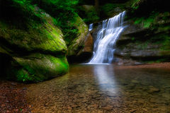 A forest waterfall over a small cliff Stock Photography