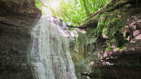 Forest waterfall in sunny summer day with sudden rain stock video