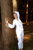 In the forest wearing white. Against a tree stock images