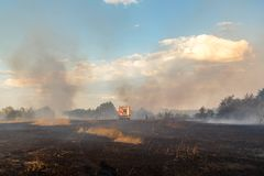 Forest wildfire due to dry windy weather. Fire engine with firefighters handling flame, Blue sky covered with heavy toxic smoke royalty free stock photography