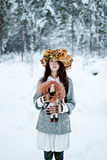 Forest woman with autumn leaves and little doll in white snow winter Royalty Free Stock Image