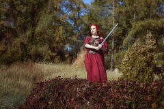 In the forest, a woman with a sword. Stock Photo