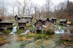 Forest with wooden water mills built on a fast and clear river in the famouse touristic site. Historical village near city Jajce in Bosnia and Herzegovina Stock Images