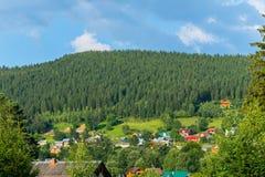 Foresta attillata densa su una collina vicino ad un villaggio carpatico con i tetti colorati fotografia stock