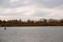 Foresta della sponda del fiume e superficie increspata dell'acqua su priorità alta con il segnale del fiume Immagini Stock Libere da Diritti