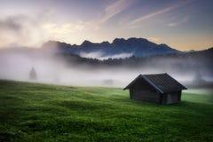Foresta di Geroldsee con bella alba nebbiosa sopra i picchi di montagna, alpi bavaresi, Baviera, Germania Fotografia Stock