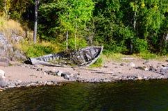 Foresta nordica e vecchia barca su una riva del lago Fotografia Stock