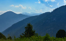 Forested area and rising mountain ranges Royalty Free Stock Photography