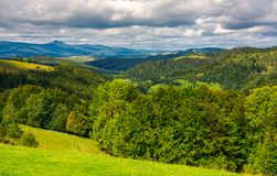 Forested hills of Carpathian mountains. Wonderful landscape in early autumn on a cloudy day. Pikui mountain in the far distance Royalty Free Stock Photo