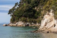 Forested klippor i den Tonga fjärden, Abel Tasman National Park Royaltyfri Bild