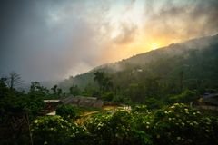 Forested mountain in low lying cloud with minority village houses, flower and faded sun.  Royalty Free Stock Photography