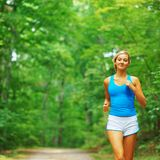 Forested Road Runner. Woman runner exercising, from a complete series of photos Royalty Free Stock Image