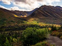 Forested Valley Overlook in Alaska. An overlook of a forested valley in Alaska.  Dappled sun and blue sky with clouds.  Hanging valley in distance, with summits Royalty Free Stock Photos