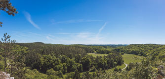 Forested valley panorama. Shot, a road can be seen dividing the forests Stock Image