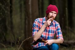 A forester with an ax in the forest. Combs his beard Stock Photo