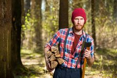 A forester with a beard carries wood and an ax. Shooting in the forest Stock Photography