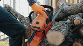 A forester desperately trying to start his chainsaw