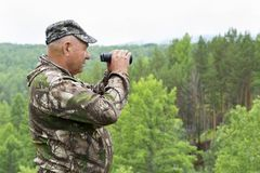 The forester looks through binoculars. Foresters went to the protection of the forest. An adult male forester examines the forest from the top of the mountain Royalty Free Stock Photos