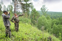 The forester looks through binoculars. Foresters went to the protection of the forest. An adult male forester examines the forest from the top of the mountain Stock Image