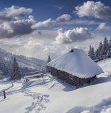 Forester's hut covered with snow in mountains Royalty Free Stock Photography