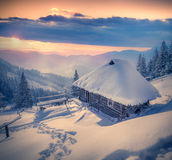 Forester's hut covered with snow in the mountains at sunrise. Stock Images
