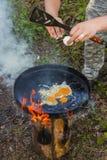 Forestier faisant frire les oeufs sur la grande casserole noire Photos libres de droits