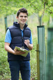 Forestry Worker With Clipboard Checking Young Trees. Portrait Of Forestry Worker With Clipboard Checking Young Trees Royalty Free Stock Photography