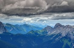 Forests and limestone peaks under dark clouds Carnic Alps Italy. Forests, ridges and rocky limestone peaks under dramatic dark storm clouds in Rinaldo mountain Stock Photos