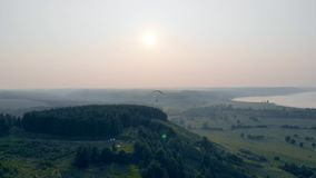 Skydiver flies in sky. Forests and plains with a ram-air parachute gliding above them