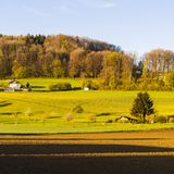 Forests and plowed fields in Switzerland. Swiss village surrounded by forests and plowed fields early in the morning. Agriculture in Switzerland, arable land and Stock Photo