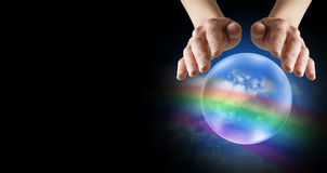 Foretelling happy days. Hands hovering over crystal ball displaying blue skies and rainbow  on a wide black background Stock Image
